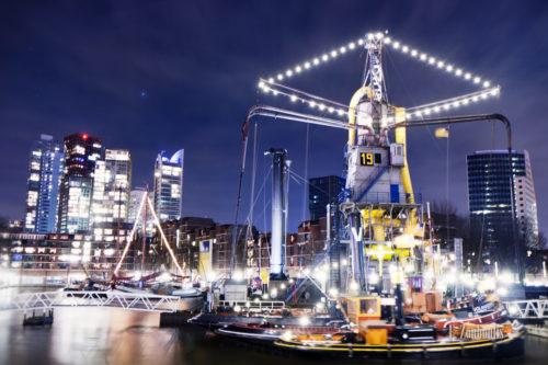 Nachtaufnahme am Hafen von Rotterdam. Im Vordergrund Schiffe auf der Anlegestelle und im Hintergrund die Hochhäuser mit funkelnden Lichtern