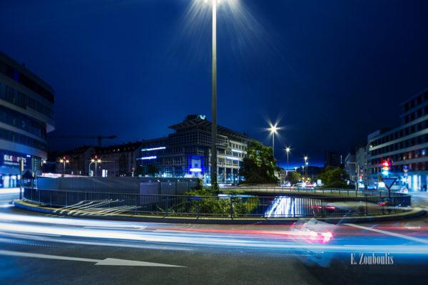 Nachtaufnahme am Österreichischen Platz in Stuttgart. Im Hintergrund sind die letzten Strahlen des Tageslichts zu sehen und im Vordergrund der Verkehr in Form von Lichtschweifen, die sich entlang des Kreisverkehrs und der B14 schlängeln