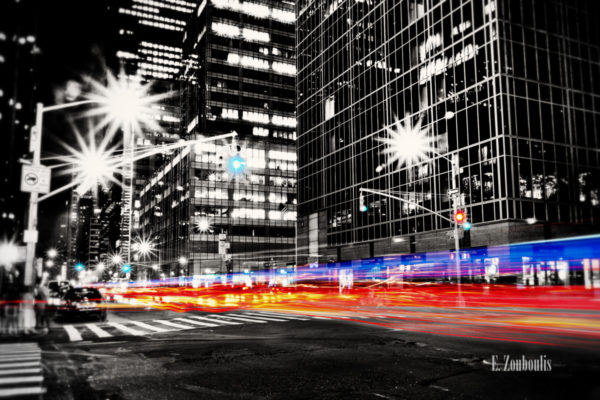 Schwarzweiß Aufnahme in New York City mit einem farbigen Lichtschweif eines Polizei Fahrzeugs, das die Straße hinunter düst