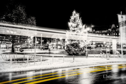Schwarzweiß Aufnahme am Marienplatz in Stuttgart. Im Vordergrund ein gelber Lichtschweif, der den Verkehr kennzeichnet und im Hintergrund ein Weihnachtsbaum und die Zahnradbahn