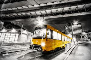 Gelbe Straßenbahn vor dem SSB Depot in Heslach auf schwarzweißer Aufnahme