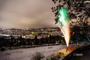 Nachtaufnahme an der Karlshöhe in Stuttgart. Im Vordergrund ein Feuerwerkskörper. Im Hintergrund Schnee und der Blick auf die Stuttgarter Innenstadt und den Fernsehturm