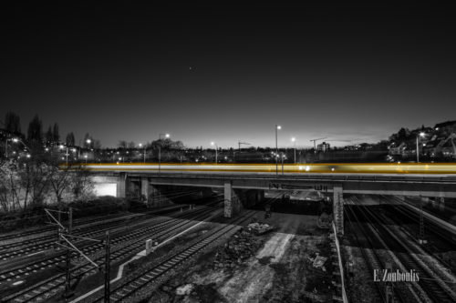 Schwarzweiß-Aufnahme am Nordbahnhof einer vorüberziehenden Straßenbahn mit einem gelben Lichtschweif