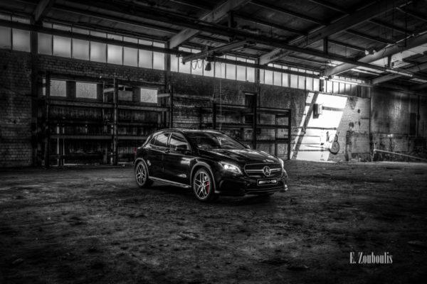 Mercedes Benz GLA 45 AMG in Schwarzweiß mit roten Elementen in einem verlassenen Fabrik Gebäude