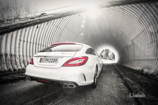 Schwarzweiß-Aufnahme eines Mercedes Benz CLS63 AMG vor einem Tunnel mit roten Elementen