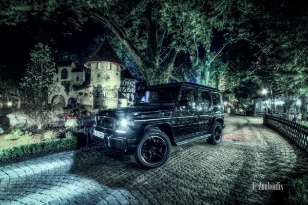 Ein schwarzer Mercedes G63 AMG vor einem Märchen-Häuschen im Europa Park