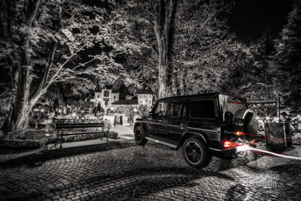 Schwarzweiß-Aufnahme eines Mercedes G63, der im Europa Park einen roten Lichtschweif hinterlässt vor einem Märchen-Häuschen