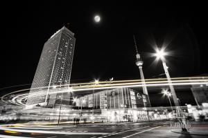 Schwarzweiß-Aufnahme am Alexanderplatz in Berlin. Die Dynamik der Stadt bei Nacht ist in der Form eines gelb / roten Lichtschweifs zu sehen, der um die Ecke schießt. Im Hintergrund erkennt man den Fernsehturm und das Park Inn Hotel bei Vollmond