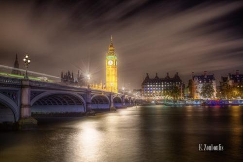 Langzeitbelichtung bei Nacht in London. Die Lichter funkeln und werden von der Themse zum Betrachter hin reflektiert. Im Himmel bewegen sich die Wolken und sorgen in dem Bild, neben den Lichtschweifen auf der Brücke für eine dynamische Komponente
