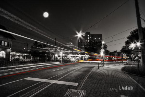 Schwarzweiß-Aufnahme am Vaihinger Bahnhof mit vorbeiziehendem Bus in Form roter und gelber Lichtschweife im Vordergrund des Pullman Hotel und des Vollmonds
