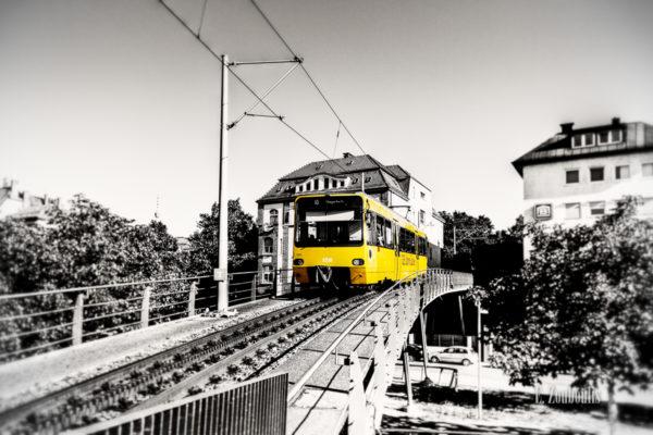 """Schwarzweiß-Aufnahme an der Brücke der Zahnradbahn am Marienplatz in Stuttgart mit gelber """"Zacke"""""""