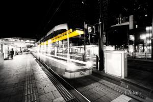 Schwarzweiß-Aufnahme einer rasenden Tram in Rotterdam. Ein Geisterzug, der einen gelben Lichtschweif hinter sich her zieht