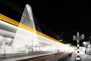 Schwarzweiß-Aufnahme einer vorbeiziehenden Straßenbahn, die am Hauptbahnhof Rotterdam einen Lichtschweif hinterlässt