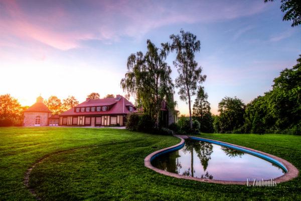 Aufnahme bei Sonnenuntergang an der Villa Schwalbenhof in Gärtringen. Im Vordergrund ist der Teich und die Wiese zu sehen und links im Bild die Villa an der sich so langsam die Sonne herablässt