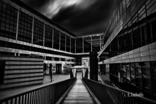 Schwarzweiß-Aufnahme an der LBBW in Stuttgart. Blick die Treppe hinunter und in den Himmel, der durch die lange Belichtungszeit die Wolken wie einen Nebel vorbeizuschicken scheint