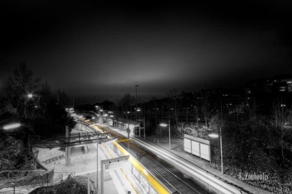 Schwarzweiß-Aufnahme am Herderplatz in Stuttgart. Eine Geister - Straßenbahn hinterlässt einen gelben Lichtschweif