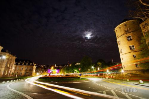 Nachtaufnahme vor dem Kreisverkehr am Schlossplatz Stuttgart. Blick Richtung Charlottenplatz über den Verkehrsknotenpunkt, der von Lichtschweifen umkreist wird bei Vollmond