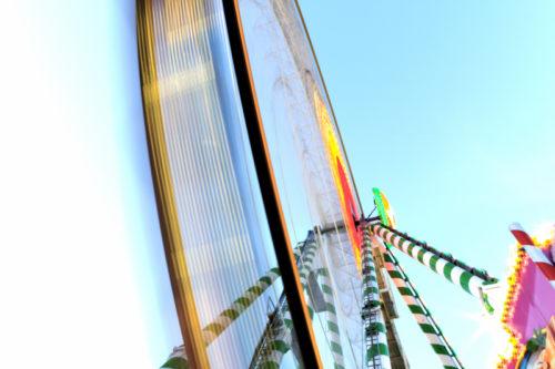 Langzeitbelichtung auf dem Cannstatter Wasen vor einem Riesenrad, dessen Bewegung sichtbar wird