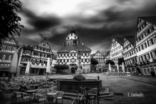 Schwarzweiß-Aufnahme am Marktplatz in Herrenberg. Im Vordergrund der Brunnen vor dem Rathaus der Stadt