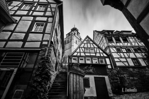 Schwarzweiß-Aufnahme in Herrenberg mit Blick über die alten Fachwerkhäuser auf die Stiftskirche am Schloßberg