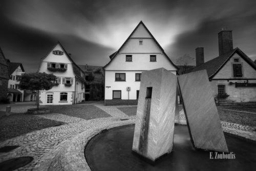 Schwarzweiß-Aufnahme am Marktplatz in Gärtringen mit dem Brunnen im Vordergrund