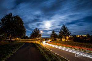 Nachtaufnahme in Gärtringen. Ein rot / weißer Lichtschweif verschwindet unter der Brücke, auf der ein Zug ebenfalls einen Light-Trail hinterlässt