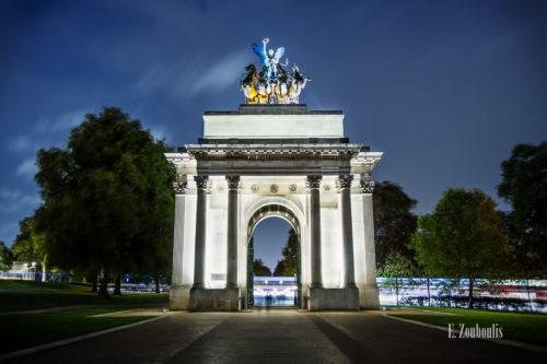 Abendaufnahme am Greeen Park in London, Großbritannien. Die Menschen laufden durch den Wellington Arch hindurch. Im Hintergrund hinterlässt der Verkehr Lichtschweife