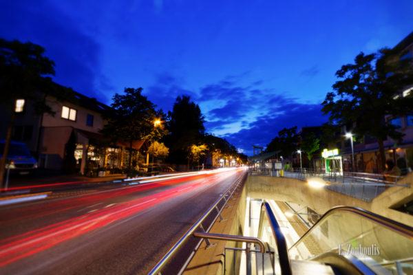 Abendaufnahme in der Kirchheimer Straße in Stuttgart Sillenbuch. Links im Bild der Verkehr in Form von rot / orangenen Lichtschweifen. Rechts geht es durch U-Bahn Haltestelle hinab