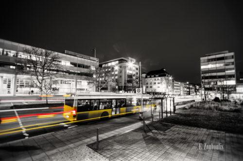 """Schwarzweiß Aufnahme vor dem Katharinenhospital in Stuttgart. Ein gelber """"Geisterbus"""" hinterlässt rote und gelbe Lichtschweife beim einfahren in die Haltestelle"""