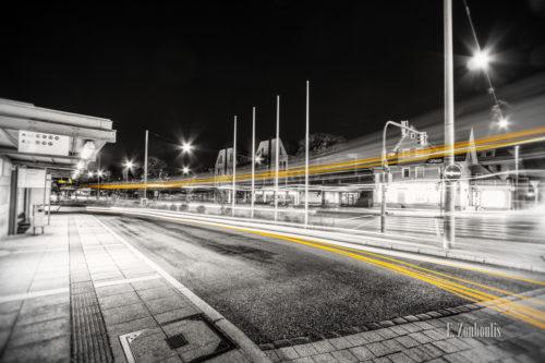 Schwarzweiß Aufnahme in der Löffelstraße am Busbahnhof in Degerloch, Stuttgart. Ein vorbeiziehender Bus ist in der Form eines gelben Lichtschweifs zu sehen