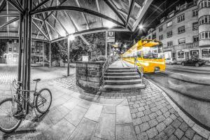 Rundum Aufnahme in Schwarzweiß am Bihlplatz in Stuttgart. Im Vordergrund ist ein Fahrrad zu sehen und in der Mitte des Bildes eine einfahrende Straßenbahn der Linie U1 in gelber Farbe