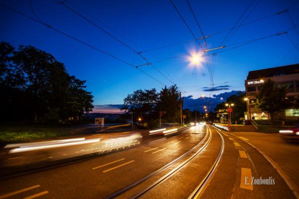 Abend-Aufnahme zur Blauen Stunde am Bubenbad in Stuttgart. Im Vordergrund sieht man die Straßenbahn-Schienen und die Fahrzeuge, die am Betrachter vorbeifahren. Links in der Mitte ist schemenhaft die Stuttgarter Innenstadt zu sehen