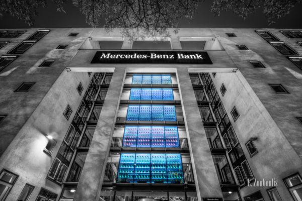 Schwarzweiß Aufnahme an der Fassade der Mercedes Benz Bank am Pragsattel in Stuttgart. In den Fenstern sieht man viele farbige Eulen. Ein Kunstwerk von Prof. Ottmar Hörl. 10000 davon wurden zum Anlass der Olympischen Spiele nach Athen getragen