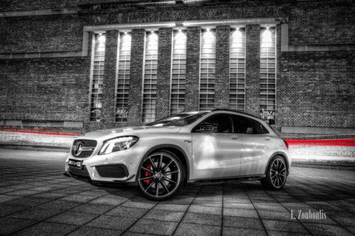 Nachtaufnahme eines Mercedes Benz GLA 45 AMG. Im Hintergrund ein roter Lichtschweif