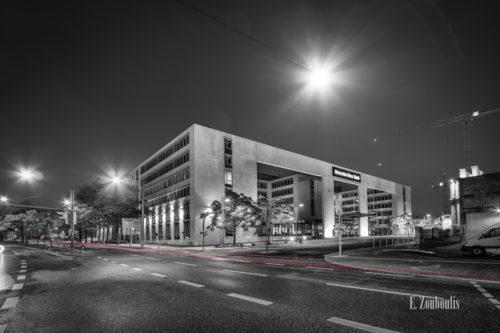 Schwarzweiß Aufnahme vor dem Gebäude der Mercedes Benz Bank am Pragsattel, Stuttgart. Im Vordergrund ist ein roter Lichtschweif zu sehen, der den Verkehr erkennbar macht