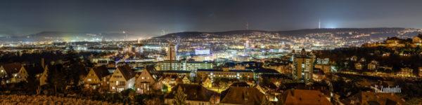 Panorama Aufnahme bei Nacht mit Blick über die Innenstadt von Stuttgart. In der Mitte des Bildes befindet sich die Stadtbibliothek. Links im Hintergrund der Gasturm und rechts auf dem Berg der Fernsehturm