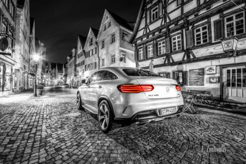 Schwarzweiß Aufnahme in der Altstadt von Esslingen. Im Vordergrund ein Mercedes GLE mit roten Heckleuchten auf einer gepflasterten Straße vor schönen Fachwerkhäusern