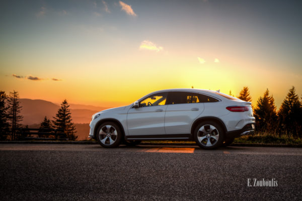 Sonnenuntergang im Schwarzwald. Die Sonne steht tief hinter einem Mercedes GLE. Seitlich sind die Nadelbäume und links im Bild die Silhouette der Berge zu sehen