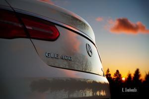 Die untergehende Sonne und die Nadelbäume des Schwarzwalds spiegeln sich am Heck eines Mercedes GLE