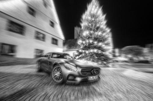 Nachtsaufnahme am Markplatz in Gärtringen mir einem Mercedes Benz AMG GTS vor einem Christbaum. Dynamisches Bild durch einen Zoomburst-Effekt