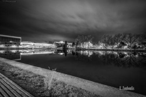 Schwarzweiß Aufnahme bei Nacht am See in Böblingen. Links im Bild die Kongresshalle, die sich im Wasser spiegelt