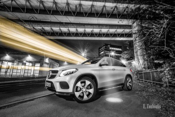 Schwarzweiß Aufnahme mit einem gelben Lichtschweif, der eine vorbeifahrende Straßenbahn kennzeichnet und roetn Elementen der Heckleuchten eines weißen Mercedes GLE unter einer Brücke in Stuttgart Südheim. Bild entstanden auf Einladung von Mercedes Benz