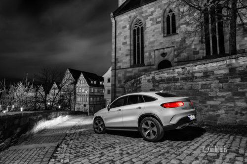 Schwarzweiß Aufnahme mit roten und blauen Elementen bei Nacht eines weißen Mercedes GLE in der Altstadt von Böblingen. Im Vordergrund das Fahrzeug auf dem Pflasterstein, im Hintergrund die Kirche und die Fachwerkhäuser am Marktplatz. Bild entstanden auf Einladung von Mercedes Benz