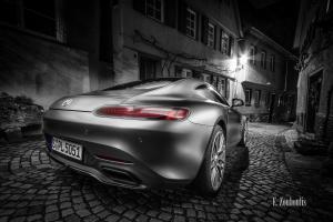 Schwarzweiß Aufnahme mit roten und blauen Elementen eines Mercedes AMG GTS in der Altstadt von Esslingen bei Nacht. Im Vordergrund das Heck des AMG auf dem Pflasterstein und im Hintergrund die charakteristischen Häuser Esslingens. Bild entstanden auf Einladung von Mercedes Benz
