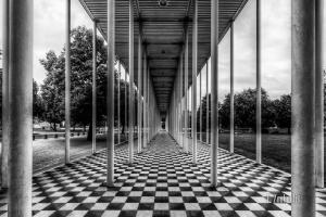 Schwarzweiß Aufnahme an der Wandelhalle in Böblingen. Im Vordergrund die schwarz/weißen Steine und die Säulenm die in die Mitte des Bildes zusammenlaufen