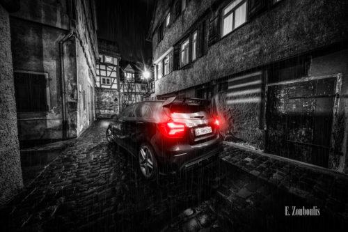 Nachtaufnahme in Schwarzweiß mit roten Heckleuchten einer schwarzen Mercedes AMG A-Klasse. Im Vordergrund der AMG auf nassem Pflasterstein. Im Hintergrund die Fachwerkhäuser in einer kleinen Gasse in Tübingen. Bild aufgenommen auf Einladung von Mercedes Benz