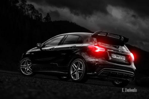 Schwarzweiß Aufnahme mit roten Heckleuchten einer schwarzen Mercedes Benz AMG A-Klasse unterwegs im Schwarzwald