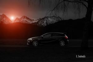 Schwarzweiß Aufnahme mit roten Lichtelementen einer schwarzen Mercedes Benz AMG A-Klasse. Im Vordergrund die Kontur des A45, im Hintergrund die verschneiten Berggipfel und die Silhouette eines Baumes