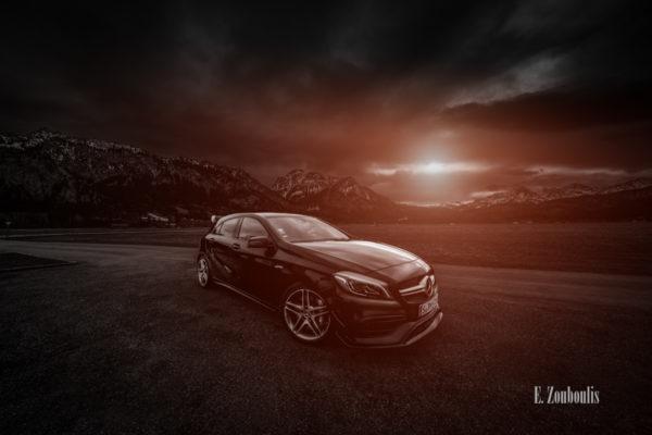 Schwarzweiß Aufnahme mit rotem Lichtelement einer schwarzen Mercedes Benz AMG A-Klasse. Im Vordergrund der A45, im Hintergrund die verschneiten Berggipfel und das Schloss Neuschwanstein