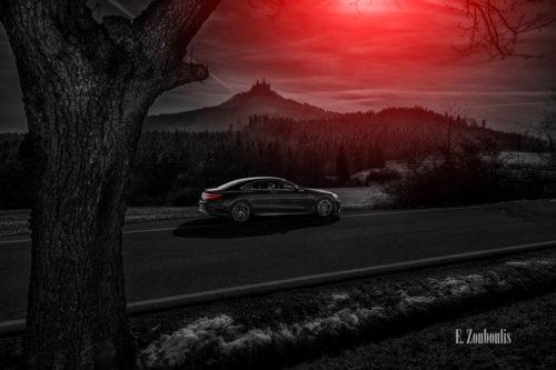 Schwarzweiß Aufnahme mit roten Elementen eines schwarzen Mercedes AMG S63 vor der Burg Hohenzollern. Im Vordergrund ist ein Baum zu sehen und etwas Schnee. In der Mitte des Bildes die S-Klasse und im Hintergrund die Burg. Aufnahme entstanden auf Einladung von Mercedes Benz